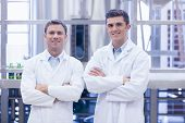 Scientist team smiling at camera with arms crossed in the factory