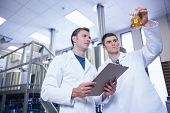 Two men in lab coat looking at the beaker with beer in the factory