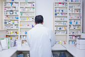 Rear view of a pharmacist working in lab coats in the pharmacy
