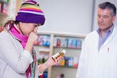Sick girl with scarf and colorful hat holding a bottle of drug in the pharmacy