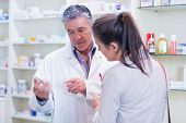 Pharmacist speaking with cheerful young customer in the pharmacy