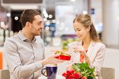 love, romance, valentines day, couple and people concept - happy young couple with red flowers and open gift box in at cafe mall