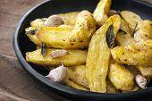 Roasted fingerling or kipfler potatoes, with sage leaves, in black dish.