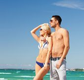 picture of happy couple in sunglasses on the beach, focus on woman