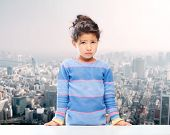people, childhood and emotions concept - sad little girl over city background