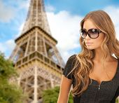 people, tourism and travel concept - beautiful young woman in shades over eiffel tower and blue sky background