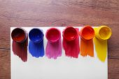Colorful paint strokes with and paint cans on white sheet of paper on wooden table background