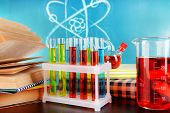 Glassware with chemical agent on desk, on green blackboard background