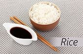 Bowl of rice and chopsticks on textile mat with space for your text