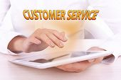 Hands holding tablet PC and Customer Service text on light background
