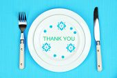 Plate with text Thank You, fork and knife on tablecloth background