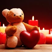 Teddy Bear with red heart and candles on dark background