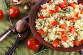Rice with walnuts and cherry tomatoes in plate on bamboo mat background