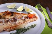 Dish of Pangasius fillet with spices and vegetables on plate and wooden table background