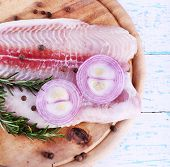 Pangasius fillet with herb and spices on cutting board and color wooden table background