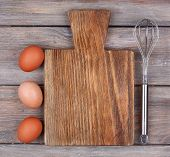 Cutting board with eggs on rustic wooden planks background