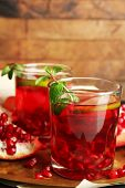 Pomegranate drink in glasses with mint on metal tray and wooden background