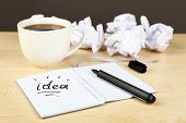 Cup of coffee with crumpled paper and note Idea in notebook on wooden table and dark background