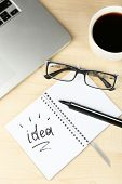 Cup of coffee with note Idea in notebook and glasses on wooden table background