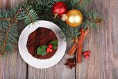 Delicious chocolate cake on saucer with holly and berry on Christmas decoration and wooden background