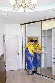Young man fixing mirrored door on corner closet in room