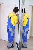 Worker fixing mirrored doors on corner sliding wardrobe in room