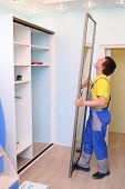 Worker setting door for sliding wardrobe in room with blue walls