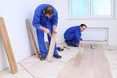 Two men in laid wood floor in white room