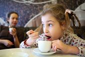 Girl hurriedly drinking tea with spoon while sitting at table in cafe