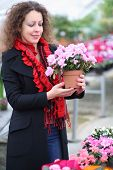 Beautiful woman holding pot with beauty flower in the greenhouse