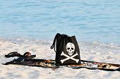 A black beach back with a smiling skull and crossbones with a towel and flip flops  on a sandy beach.