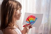 foto of gril  - Nice teen gril painting colorful rainbow near the window - JPG