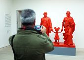 Visitor takes photo of the art work in a gallery