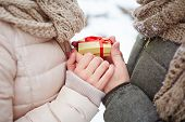Male hands holding small present while giving it to his girlfriend