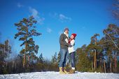 Affectionate couple in knitted winterwear enjoying weekend in forest