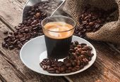 stock photo of hot coffee  - Espresso coffee in glass cup with coffee beans on wooden table - JPG