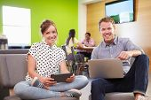 Creatives Having Informal Meeting On Sofas In Design Studio