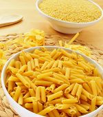 a bowl with uncooked penne rigate, some uncooked tagliatelle with its characteristic nest shape, and a bowl with pastina in the background