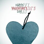 closeup of a piece of slate stone in the shape of a heart and the text happy valentines day with a vignetted effect