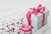 stock photo of confetti  - Gift box with pink bow and confetti in shape of heart on wooden background - JPG