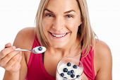 Portrait of Woman enjoying eating her yogurt and blueberries isolated on white background