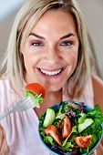 Portrait of Woman enjoying a healthy salad bowl at home