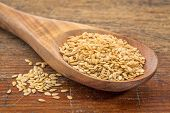 gold flax seeds on a wooden spoon against a grunge wood