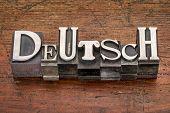 Deutsch (German) word in mixed vintage metal type printing blocks over grunge wood