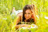 Young woman in green dress rest in the grass