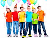 Group of happy children in colored t-shirts with balloons on a white background.