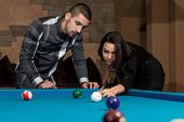 Couple Playing Pool At The Bar