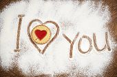 picture of home is where your heart is  - Heart and I Love You words of white flour on a wooden board - JPG
