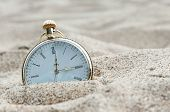 stock photo of wind up clock  - Close up photo of Pocket watch buried in sand - JPG