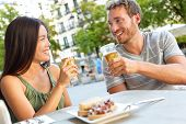 Couple eating tapas drinking beer in Madrid, Spain. Romantic man and woman enjoying local traditional food on square in Madrid. Asian woman and Caucasian man dating.